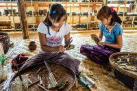 Young girls hard at work fabricating cheroot cigarettes.