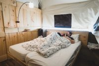 The platform tents can sleep six people. There's a room with a king-size bed, a cabinet bed for two, and another room with a bunk bed. We illuminated our room with the provided solar laterns as well as a set of string LEDs.