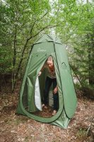 A camping toilet is located within a privacy tent.